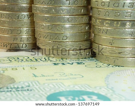 British banknotes with stack of UK pound coins - stock photo