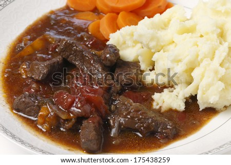British beef and tomato casserole, served with mashed potatoes and boiled carrots, closeup - stock photo