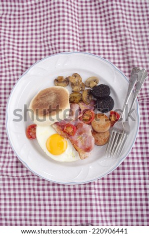 british breakfast muffin with fried egg, black and white pudding, bacon, tomato and mushroom on a plate