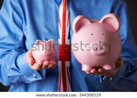 British Businessman Holding Large And Small Piggy Bank