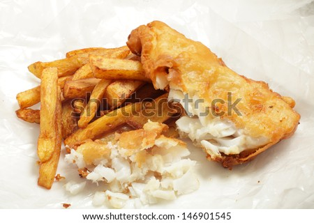 "British ""chip shop"" style fried cod in batter with chips (french fries) in a wrapping of greaseproof paper. Shot with a tilt-shift lens for maximum depth of field. - stock photo"