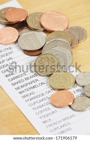 British Coins on a Receipt for Food Shopping as a concept for rising prices and the cost of living. Focus is on the coins in the middle. - stock photo