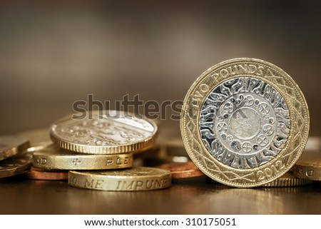 British coins over blurred background.  One and two pound coins. - stock photo