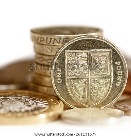 British coins, with focus on one pound.  White background. - stock photo