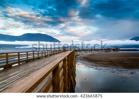 British Columbia's Salmon Arm wharf on a cloudy morning at sunrise, with low fog on the horizon. It is the longest wooden wharf in North America.