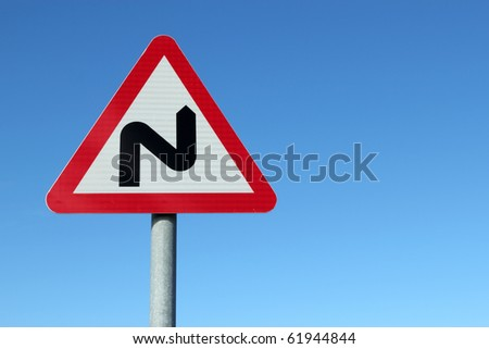 British double bend road sign and blue sky. - stock photo