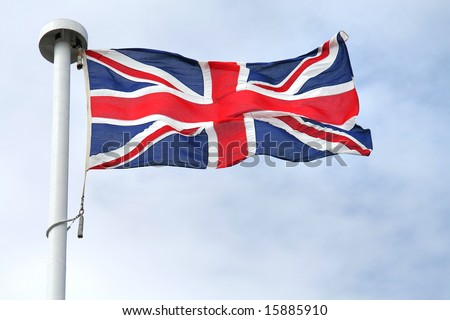 British flag on a mast, cloudy sky in background - stock photo