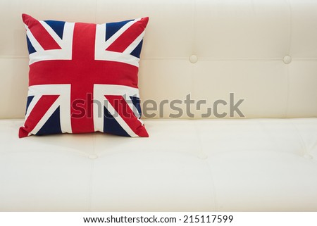 British flag pillow placed on a cream leather sofa. - stock photo