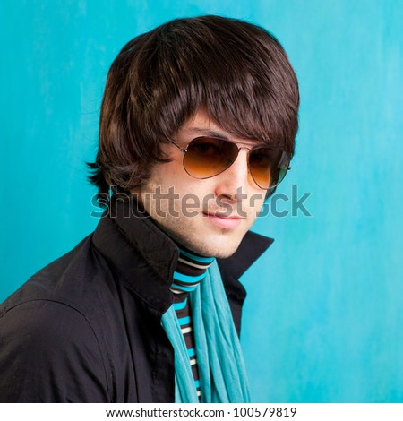 british indie pop rock look retro hip young man with sunglasses on blue - stock photo