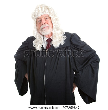 British judge in wig with hands on hips in a stern posture.  Isolated on white.