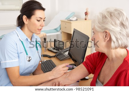 British nurse giving injection to senior woman - stock photo