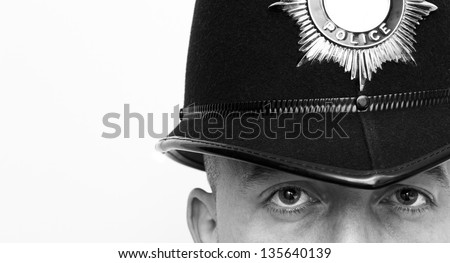 British Police Officer wearing a police helmet with copy space - stock photo
