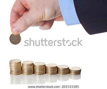 British pound sterling coins stack in columns symbolizing wealth growth with a hand puts a pound coin over it. Successful investment business concept - stock photo
