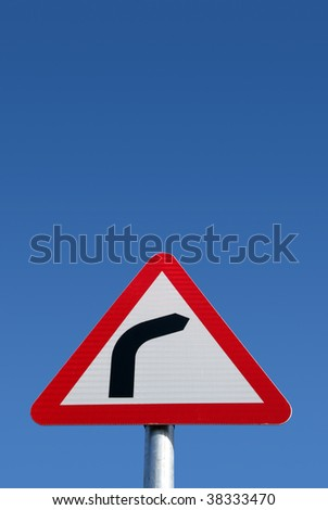 British road bend to right warning sign and a big blue sky. - stock photo