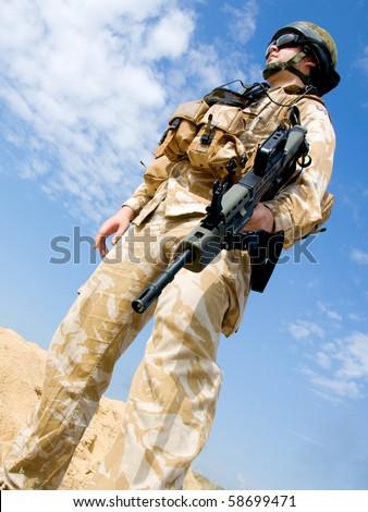 British Royal Commando in desert uniform holding his rifle - stock photo