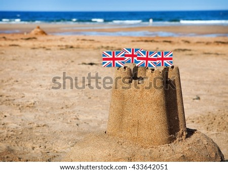 British seaside traditional sandcastle on the beach with union jack flags. - stock photo