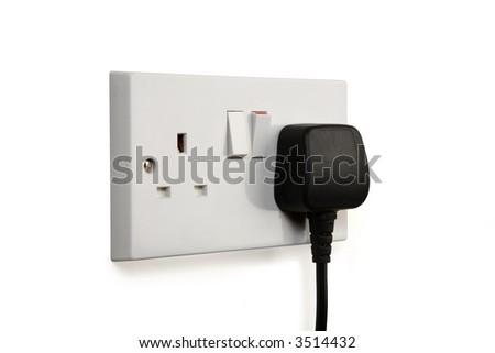 British socket and black plug. Socket turned on. - stock photo