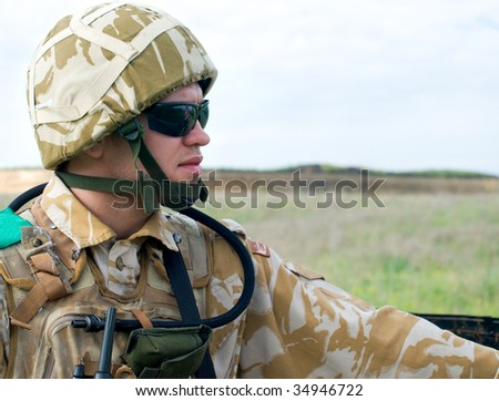 British soldier with the reflection of UK flag in glasses looking forward - stock photo