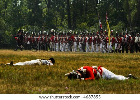 British soldiers marching during a War of 1812 battle re-enactment. Dead soldiers in the foreground.