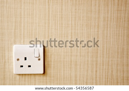 British Standard BS 1363 AC power socket at the corner of a wall - stock photo