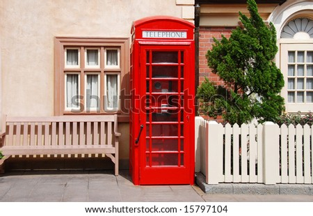 British telephone red box in front of houses - stock photo