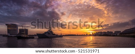 British warship from the navy is leaving the port of Amsterdam with tugboat assistance. Beautiful panorama sundown background.