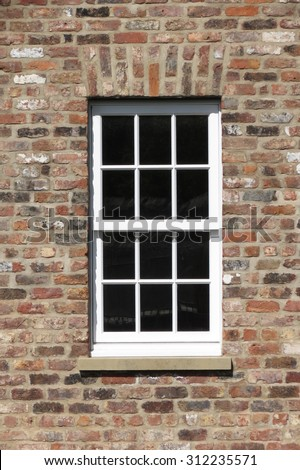British window in a brick wall - stock photo