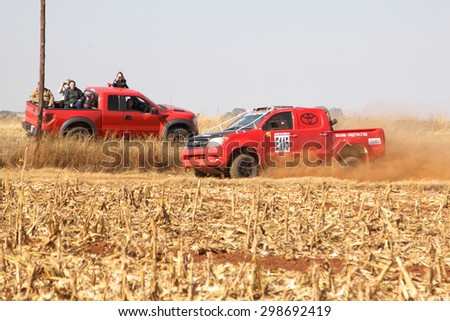 BRITS, SOUTH AFRICA - July 11:  Africa-Offroad Racing Rally,  on July 11, 2015 at Koster, North West Province, South Africa.  Red Toyota rally truck passing red spectators truck on dusty road.  - stock photo