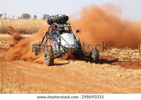 BRITS, SOUTH AFRICA - July 11:  Africa-Offroad Racing Rally,  on July 11, 2015 at Koster, North West Province, South Africa.  Custom single seater rally buggy kicking up trail of dust. - stock photo