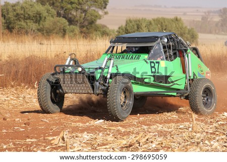 BRITS, SOUTH AFRICA - July 11:  Africa-Offroad Racing Rally,  on July 11, 2015 at Koster, North West Province, South Africa. Custom twin seater rally buggy kicking up trail of dust. - stock photo