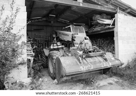 BRITTANY, FRANCE - JULY 17, 2014: Old yellow tractor with telescopic loader in the barn.  Telescopic handlers are widely used in agriculture and industry. - stock photo