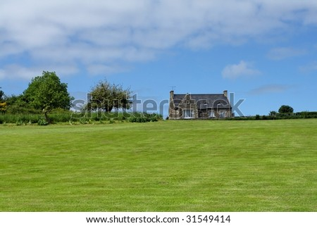 Brittany house on meadow - stock photo