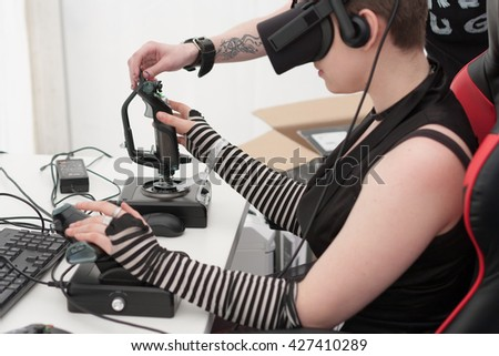 BRNO, CZECH REPUBLIC - APRIL 30, 2016: Young girl with VR - glasses sits on gaming chair and plays game on PC at Animefest, anime convention on April 30, 2016 Brno, Czech Republic
