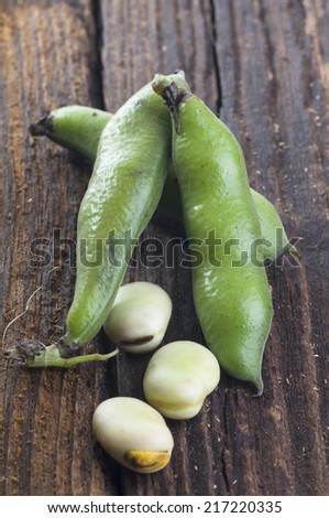 Broad beans pilled and in pods on wooden background. Vicia faba, also known as the broad bean, fava bean, faba bean, field bean, bell bean, or tic bean, is a species of bean (Fabaceae)  - stock photo