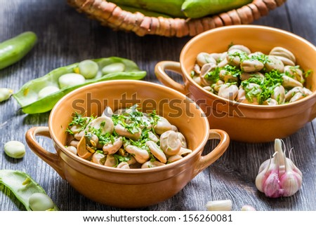Broad beans served with parsley and garlic - stock photo