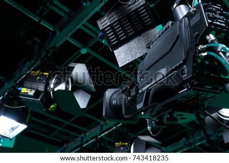 Broadcast television studio camera with LED lights on the ceiling.