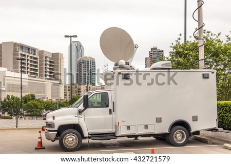 Broadcast vehicle with antennas in a parking lot