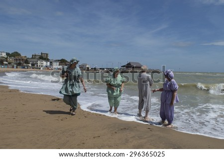 BROADSTAIRS,UK-JUNE 15: Dickens Festival members dressed in Victorian costume take part in the annual festival with a beach party, in Viking Bay, including sea bathing. June 15, 2015 Broadstairs UK - stock photo