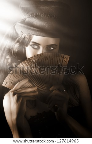 Broadway Entertainer Holding Vintage Wooden Fan While Looking Into The Stage Spotlight In A Depiction Of A Cabaret Theatre Show - stock photo