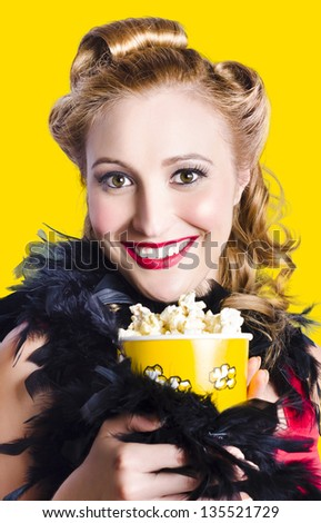 Broadway showgirl holding box of theatre popcorn during cabaret performance. Yellow background - stock photo