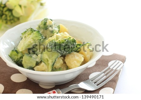 broccoli and potato salad on white background with copy space