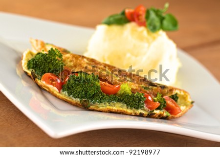 Broccoli and tomato omelet with mashed potato (Selective Focus, Focus on the broccoli floret in the front)