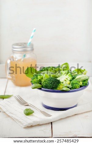 Broccoli, baby spinach and green beans salad in ceramic bowl with olive oil on a white wooden background. - stock photo