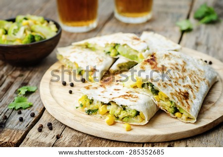 broccoli corn zucchini quesadilla on a dark wood background. the toning. selective focus - stock photo