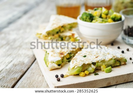 broccoli corn zucchini quesadilla on a white wood background. the toning. selective focus