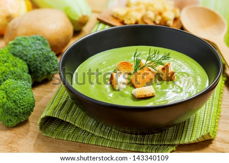 Broccoli cream soup and ingredients on table - stock photo