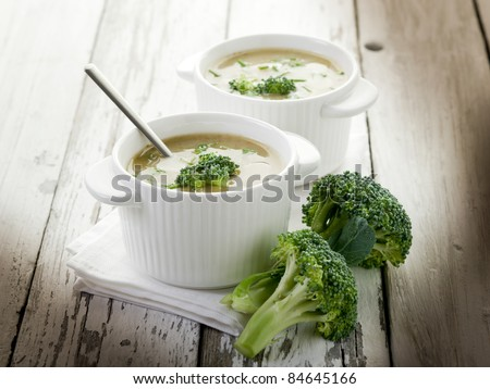 broccoli soup on bowl over wood background - stock photo