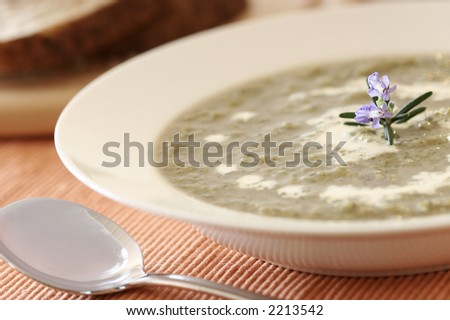 Broccoli soup.  Very shallow D.O.F.- Decoration flower/thyme in focus - stock photo