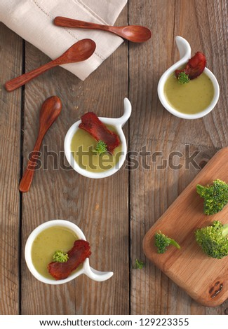 Broccoli soup with bacon in small bowl on wooden background - stock photo