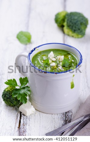 Broccoli soup with mint and feta cheese on white wooden background - stock photo